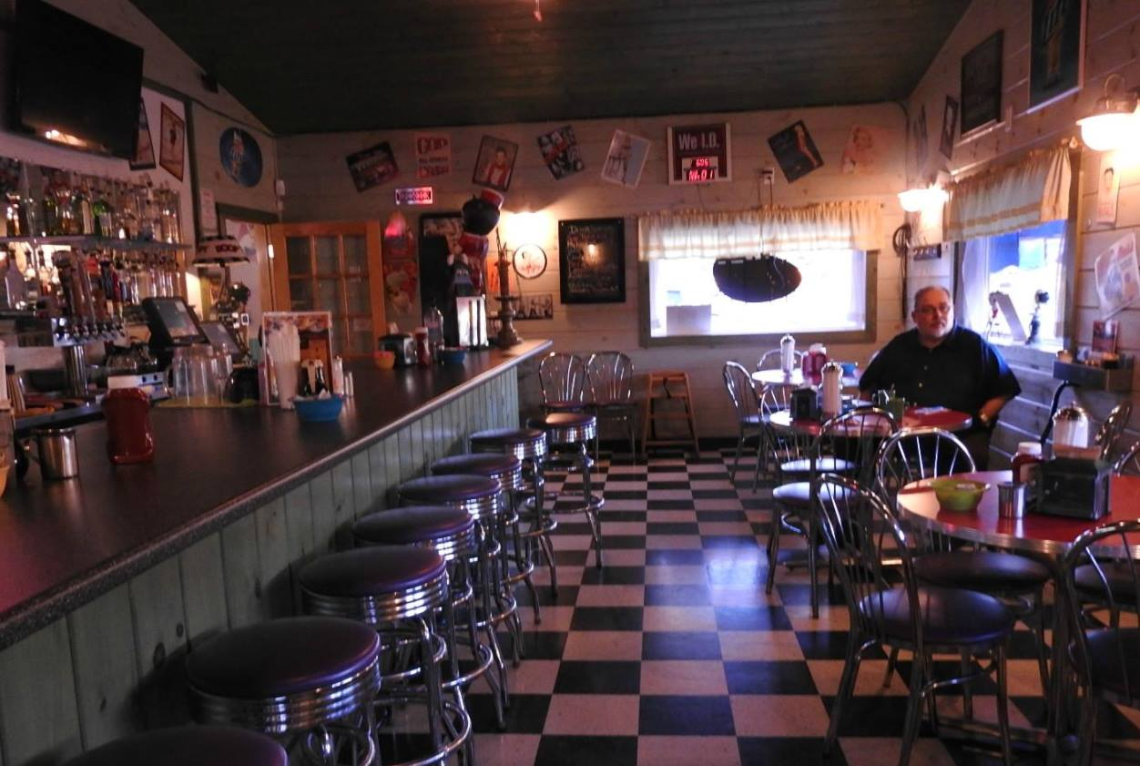 inside of purple cow with tables, chairs, and bar stools