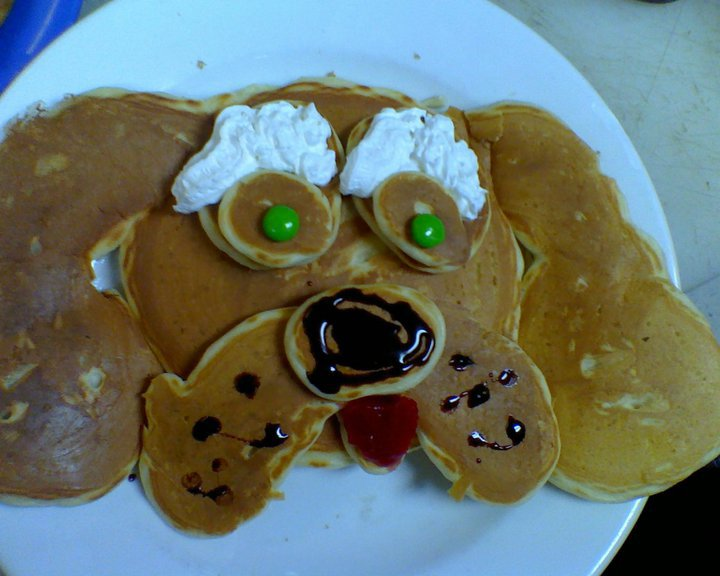 pancake in the shape of a dogs face with whipped cream and chocolate syrup