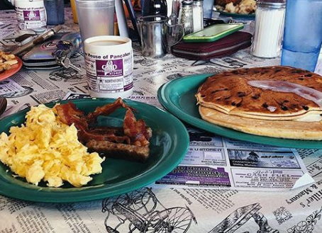 a plate of chocolate chip pancakes with a side of scrambled eggs and bacon