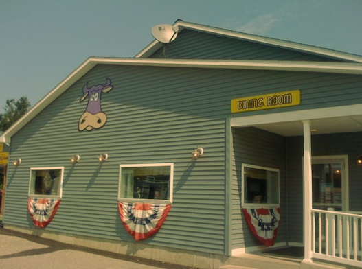 exterior of purple cow with sign and flags hanging