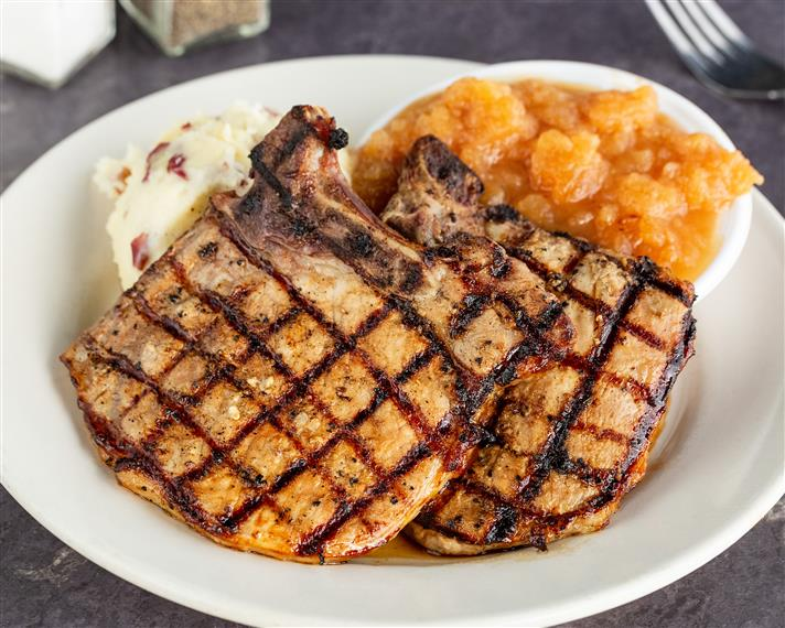 Grilled pork chops served with candied yams and mashed potatoes