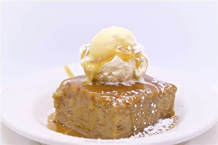 Cake topped with a vanilla scoop of ice cream and caramel sauce