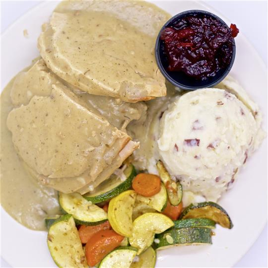 Chicken topped with gravy served with a side of zucchini and mashed potato