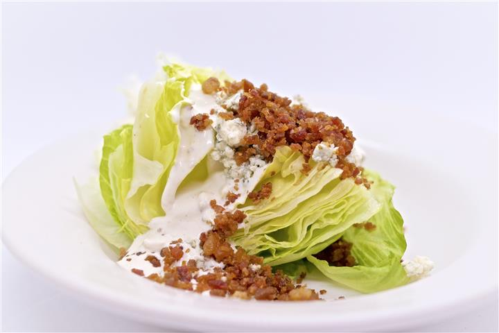 Lettuce topped with ranch sauce and meat
