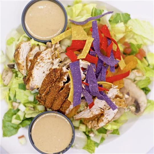 Salad topped with chicken and chip strips. Served with two sides of dressing