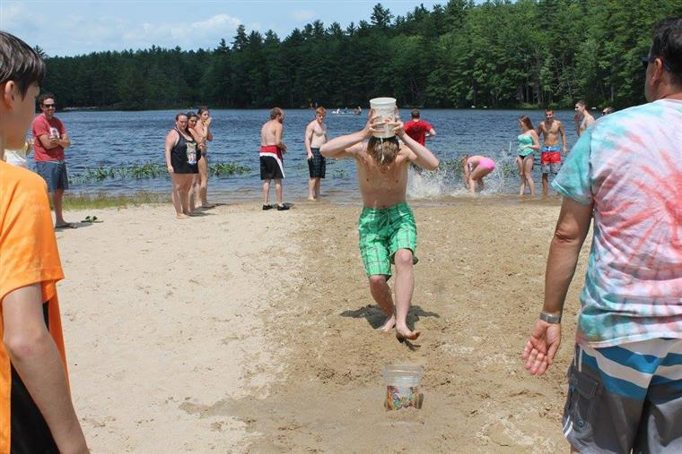group of kids playing in the sand next to a large lake