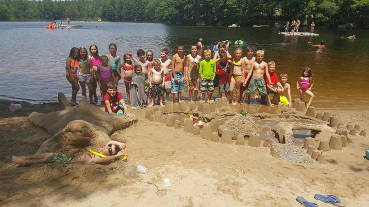groups of kids in the sand posing together showcasing their sand castles