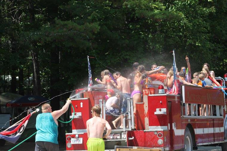 group of young kids on a fire truck having a large water gun fight