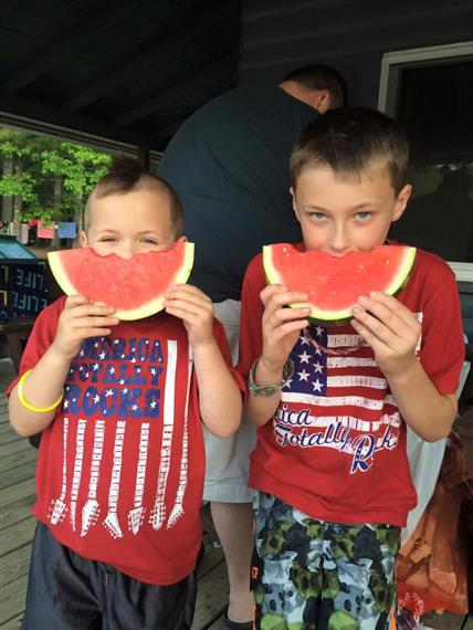 two young boys eating watermelon together