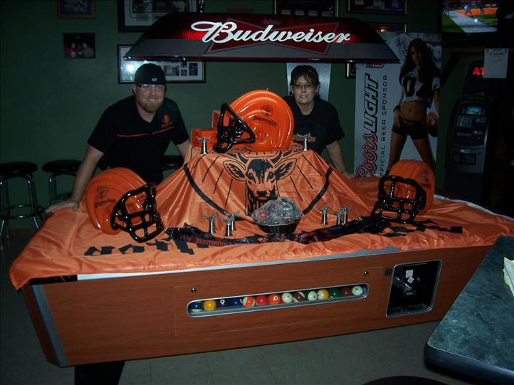 halloween decorations setup on a pool table with employees standing aorund it