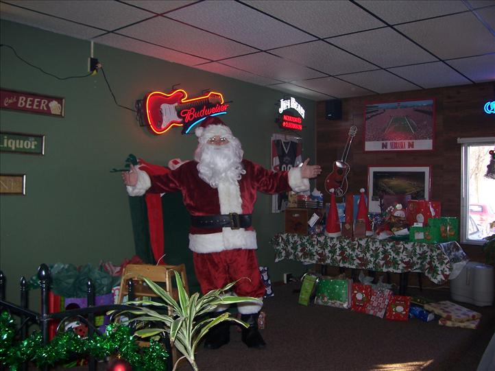person dressed up as santa clause standing in front of a chair