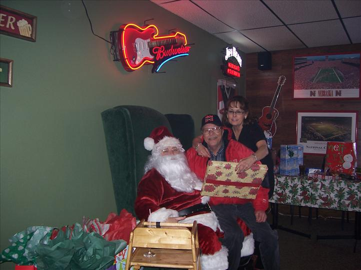 customer sitting on santas lap smiling at the camera