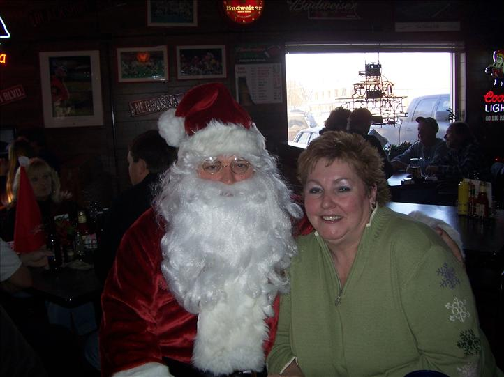 customer standing with santa clause smiling at the camera