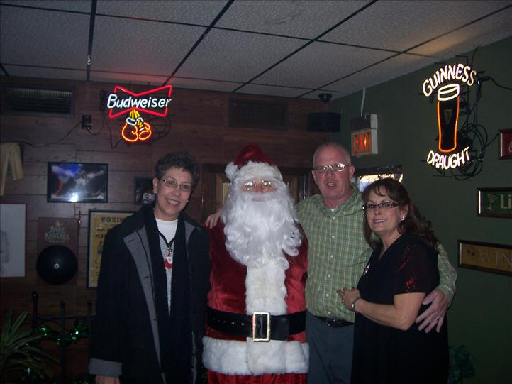 group of people standing with santa clause smiling for the camera
