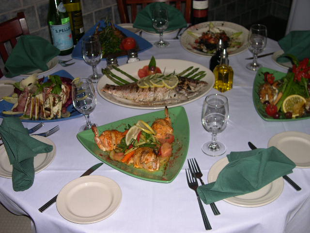 A dinner table with grilled fish, grilled shrimp and salads