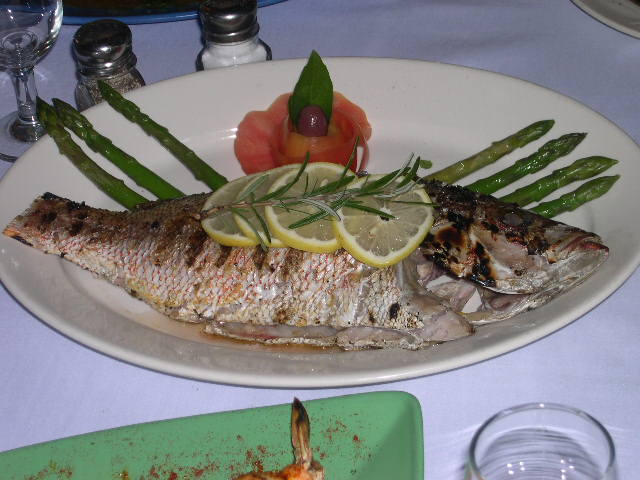 A grilled fish served with lemon, rosemary, asparagus and lemon