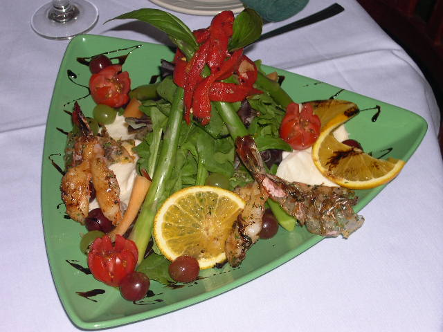 A green salad with lettuce, cherry tomatoes, shrimp, roasted red peppers, olives and fresh onion