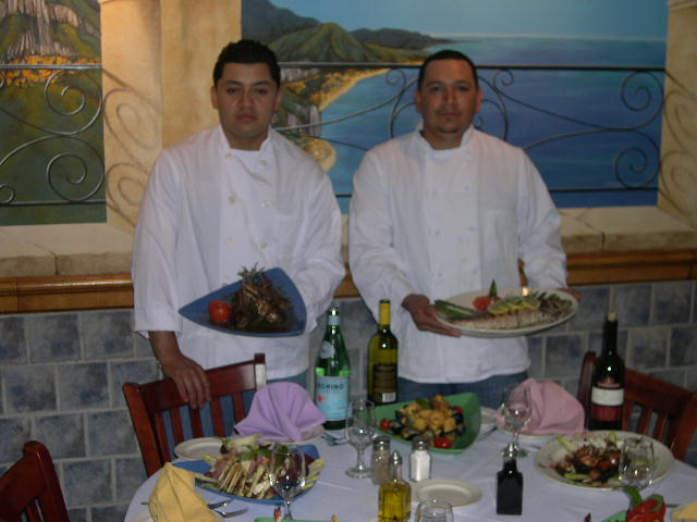 Two chef standing in front of a set table