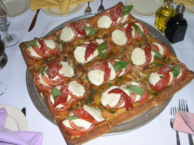 Square pizza with mozzarella, basil, tomato and roasted red peppers