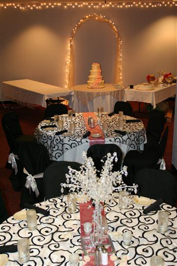 several decorated tables, one has a fancy tiered cake
