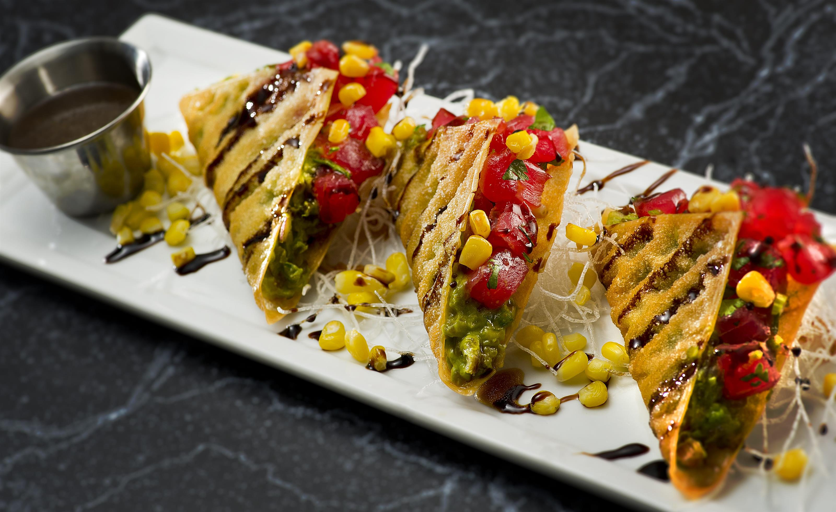 sushi tacos with avocado, tuna, corn, cilantro and a brown sauce in a crispy tortilla served with more sauce on the side