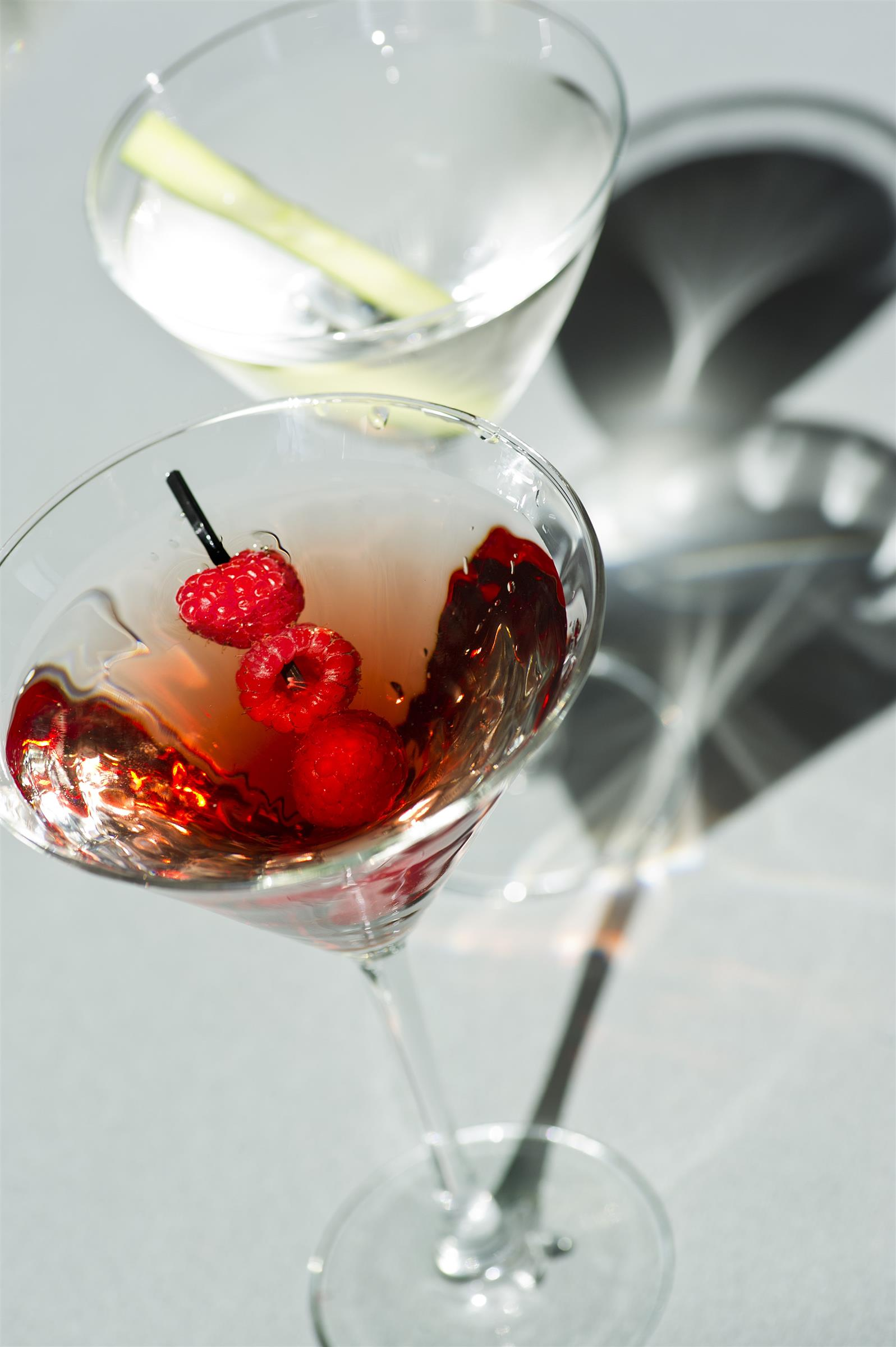 one cocktail with raspberry as a garnish next to another cocktail with lemongrass as a garnish