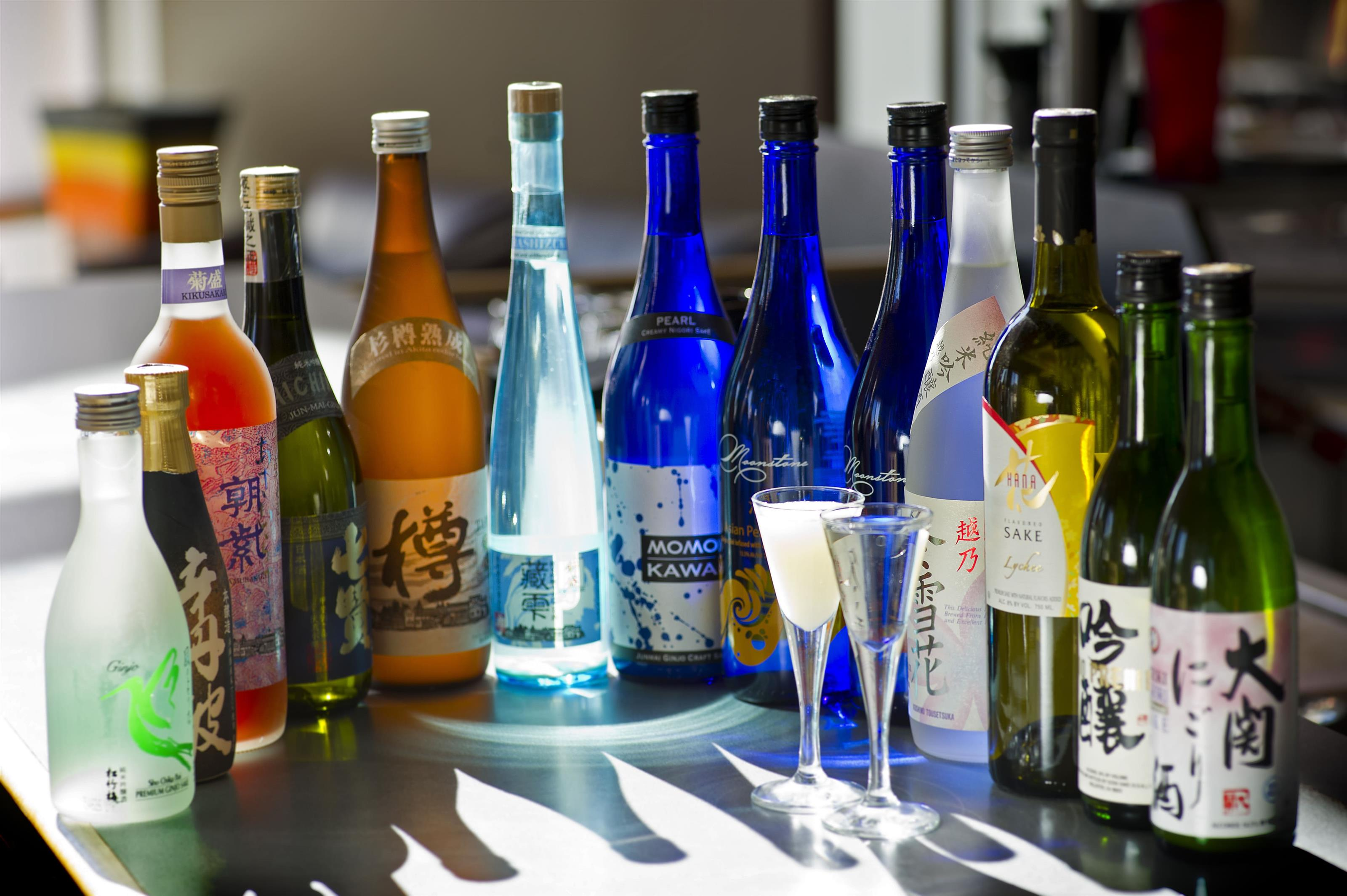 various bottles of wines, liquors and sake with 2 glasses filled