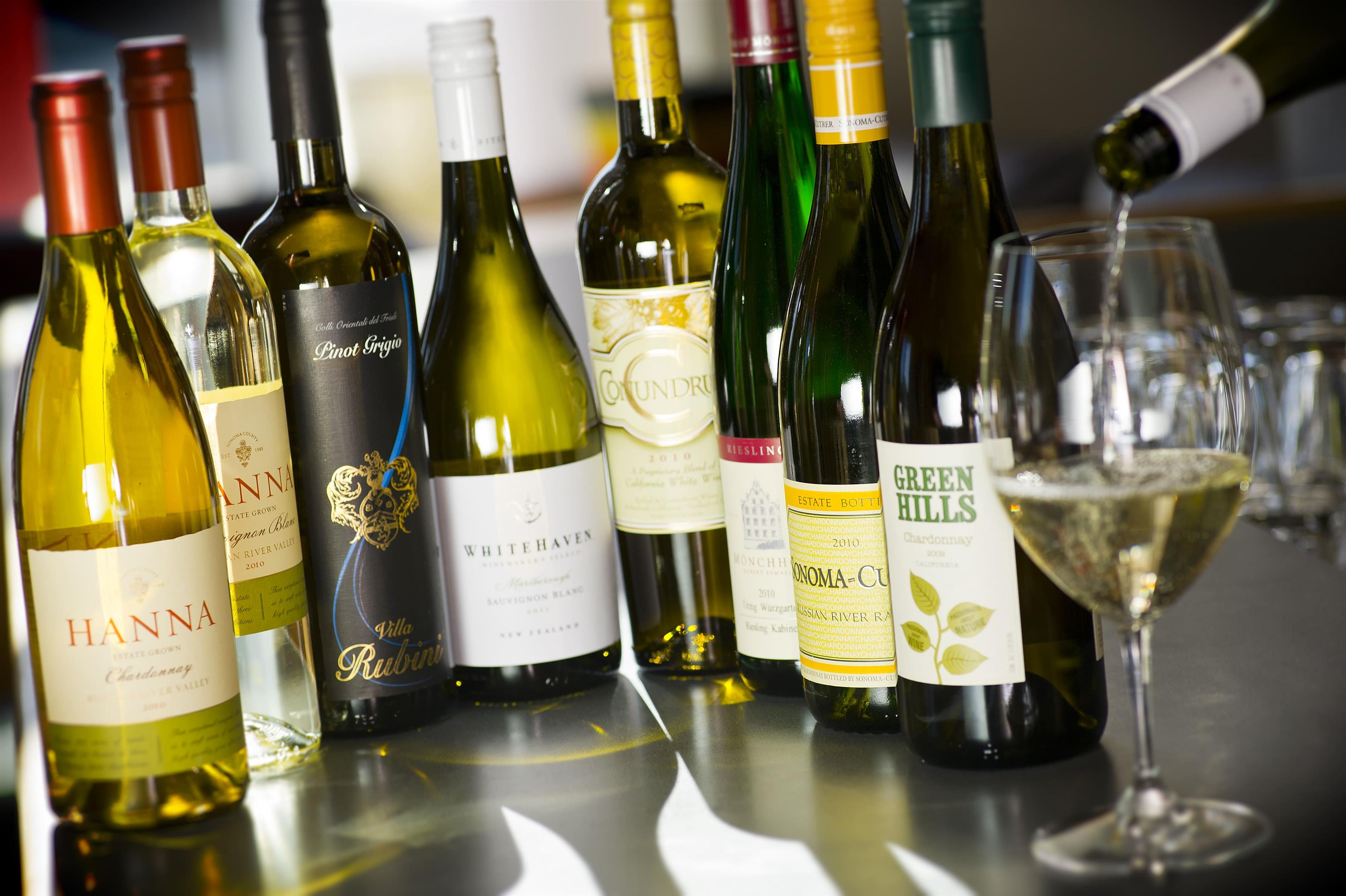 various bottles of white wine with one glass being poured