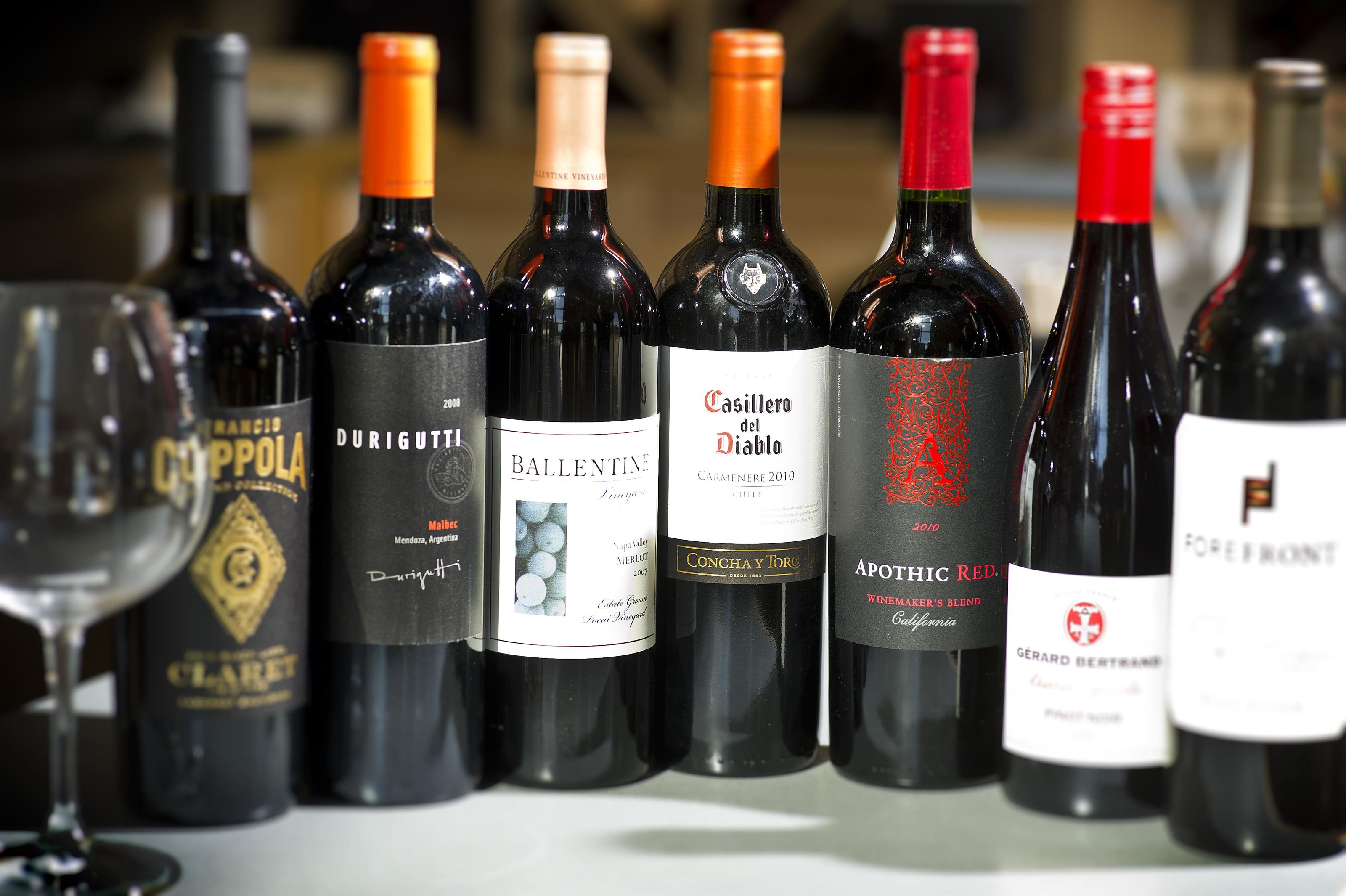 various bottles of red wine with a glass  over to the side