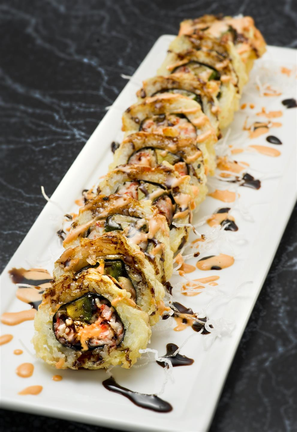 crab sushi roll with smoked eel and spicy mayo, covered and fried in tempura with a brown sauce drizzled on top