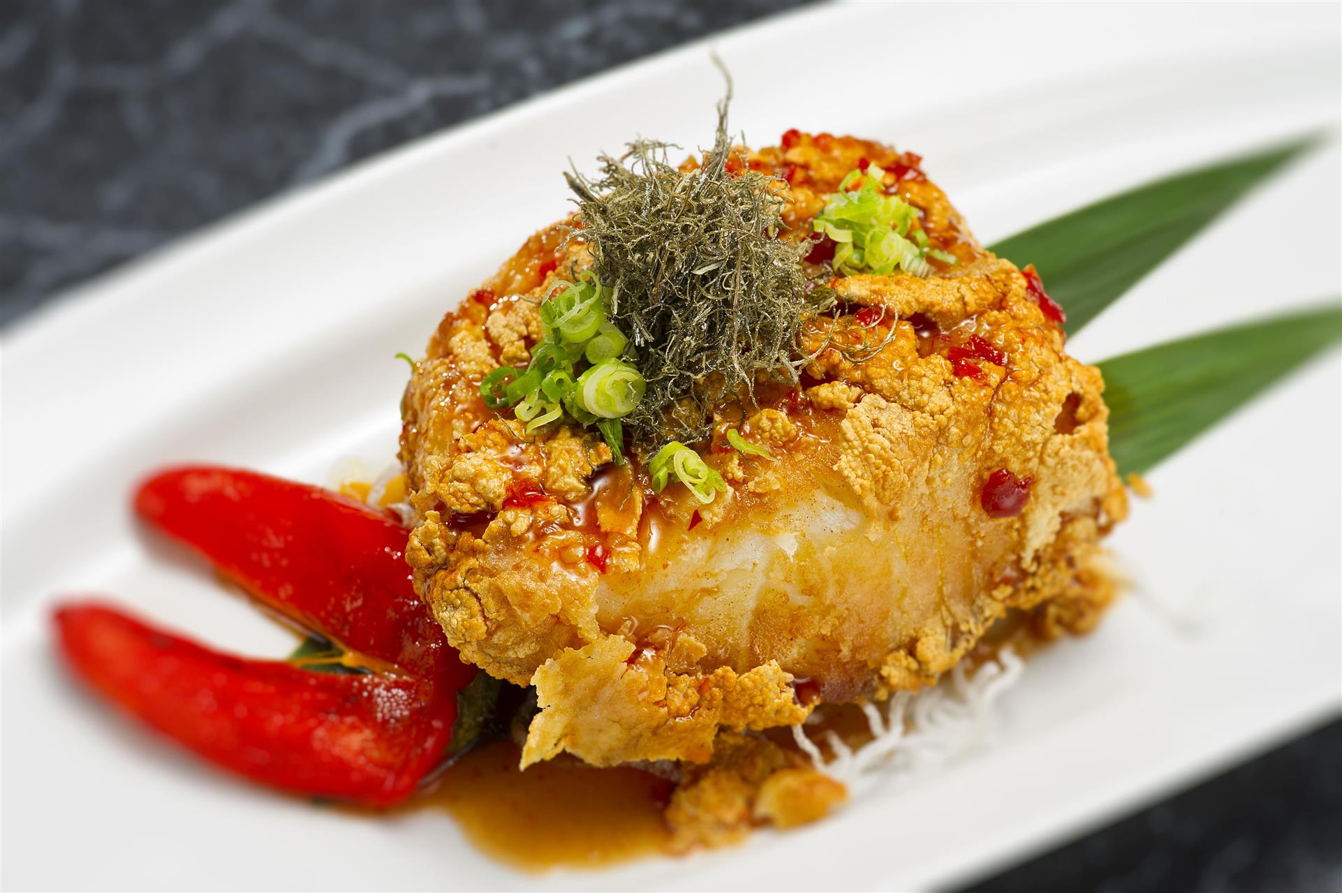 chunk of tempura white fish with scallions and chili flakes on top
