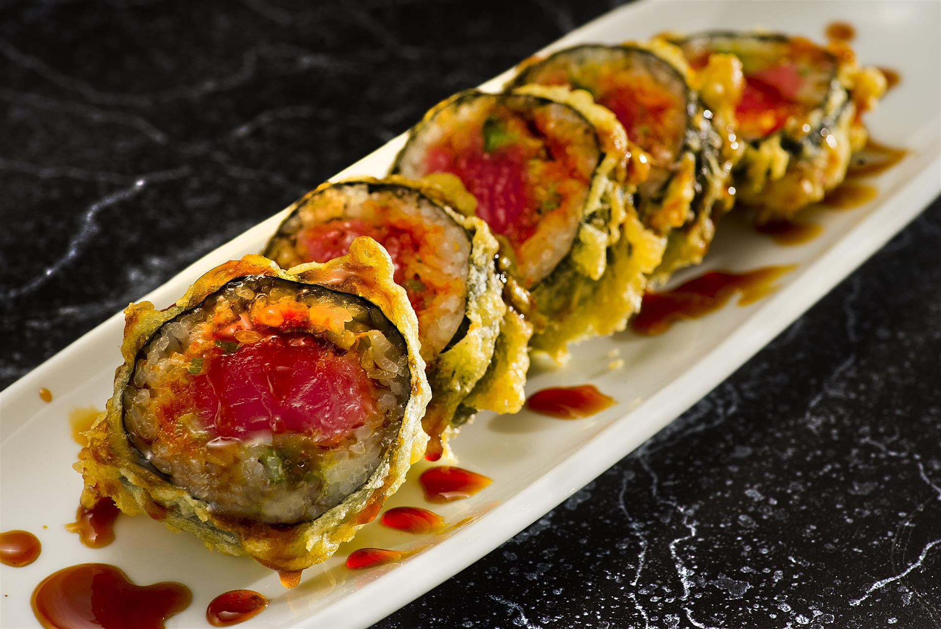 sushi roll with tuna, avocado, salmon roe, covered and tempura fried with a brown sauce