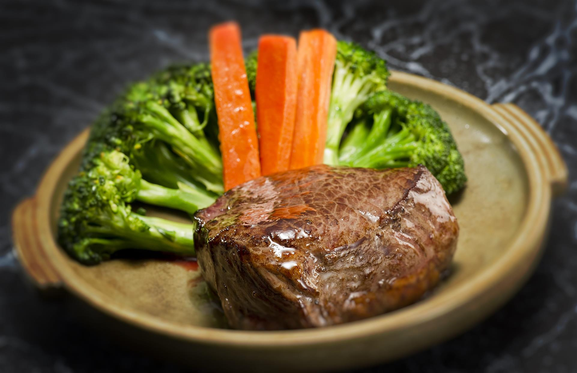 chunk of beef and broccoli served with carrot sticks