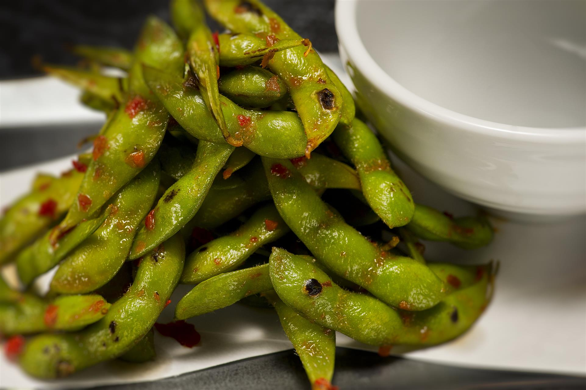 edamame beans with a spicy brown sauce on top