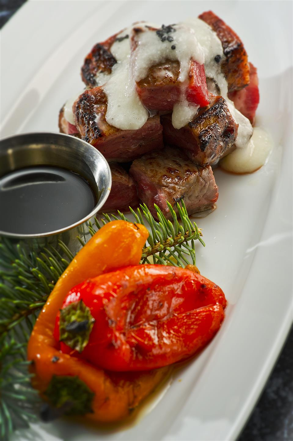 seared steak pieces served with a creamy sauce and roasted peppers