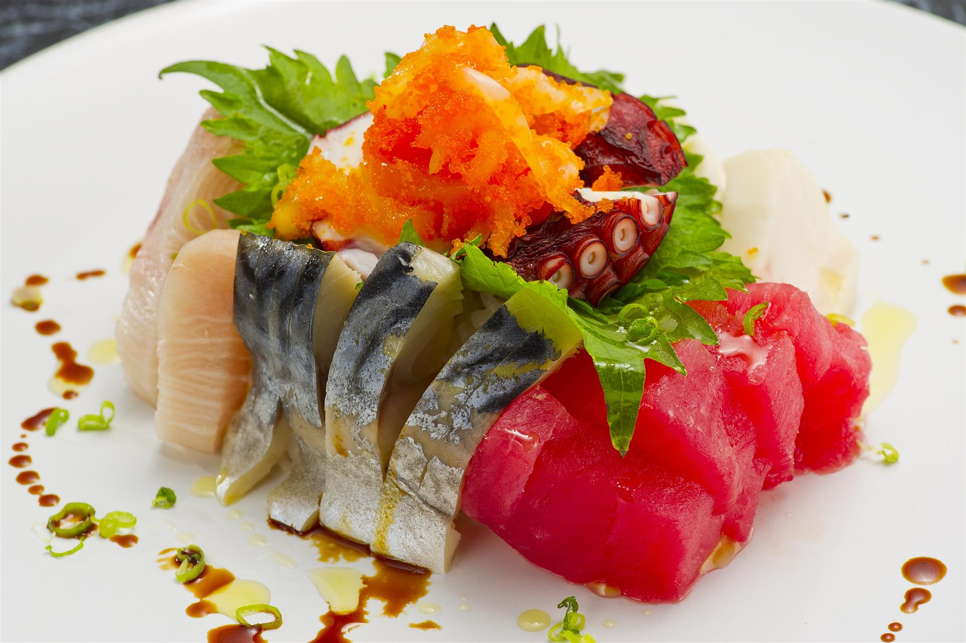 various types of sashimi with octopus chunks and salmon roe on top