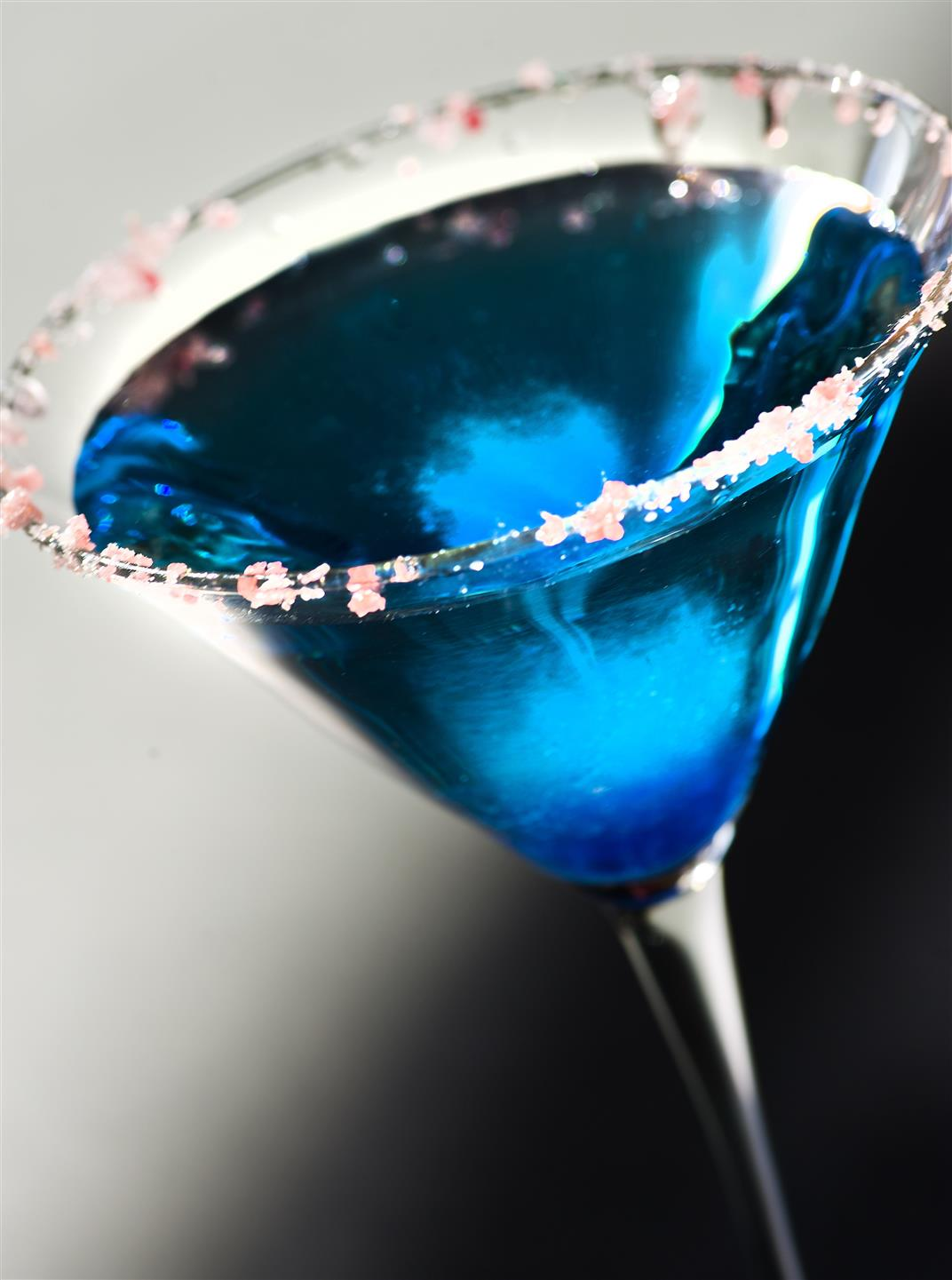 blue cocktail being poured into a glass with candy on the rim