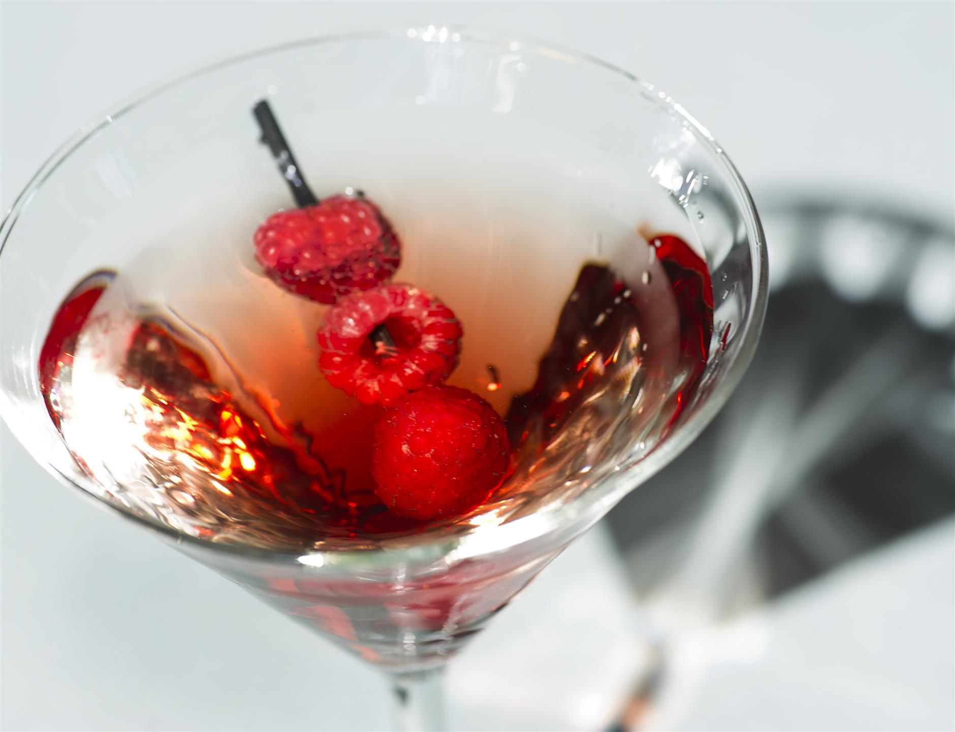 martini with raspberries as a garnish