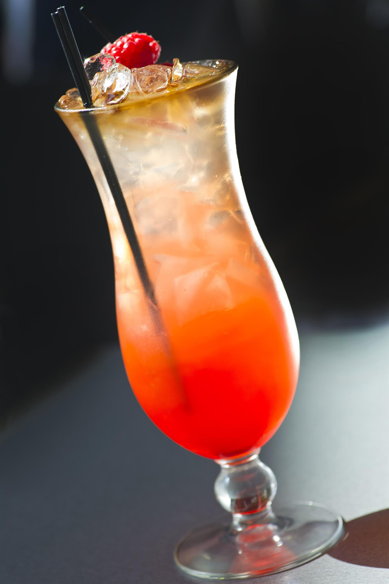 mixed drink in a tall glass with a raspberry as a garnish