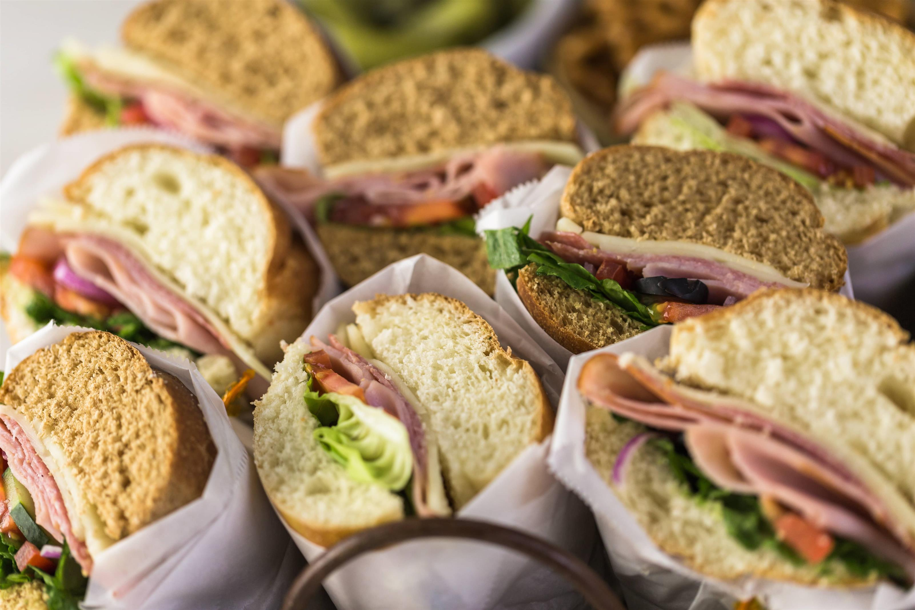An assortement of sandwiches wrapped in paper