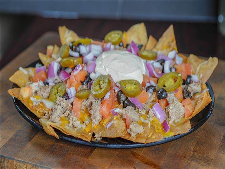 Corn chips topped with smoked shredded pork, cheddar and mozzarella cheeses, olives jalapenos, onions, tomatoes and seasoned sour cream