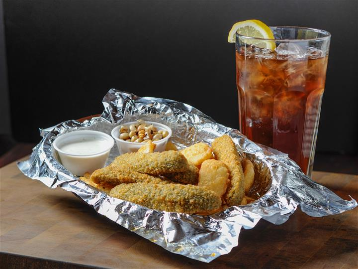 Fried appetizers served on aluminum foil, served with dipping sauce, and a glass of iced tea