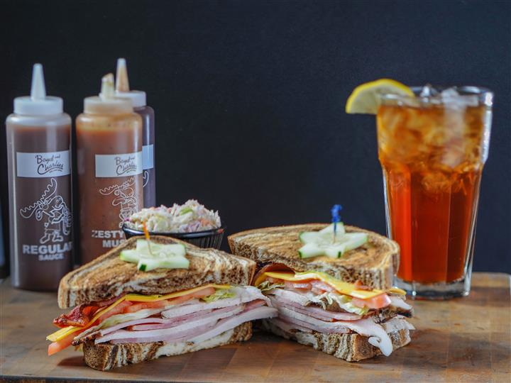 Sandwich served with sauces and side salad, with a glass of iced tea