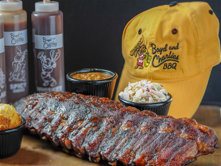 Ribs rubbed with seasonings and slowly smoked, served with beans, side salad, sauces, by a jockey hat