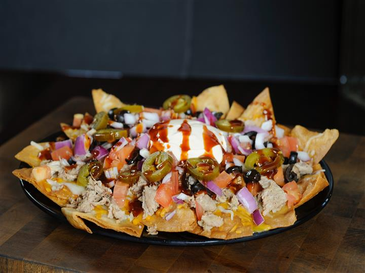 Corn chips topped with smoked shredded chicken cheddar and mozzarella cheeses, olives jalapenos, onions, tomatoes and seasoned sour cream