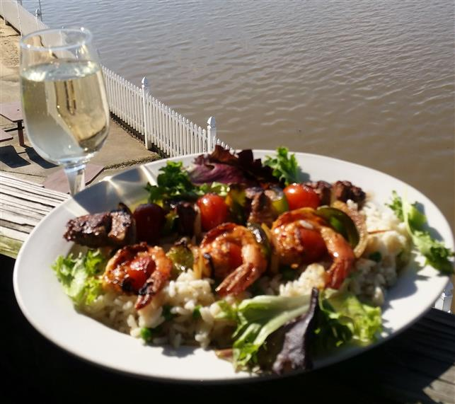 Shrimp and meat on skewers with vegetables with glass of wine overlooking water