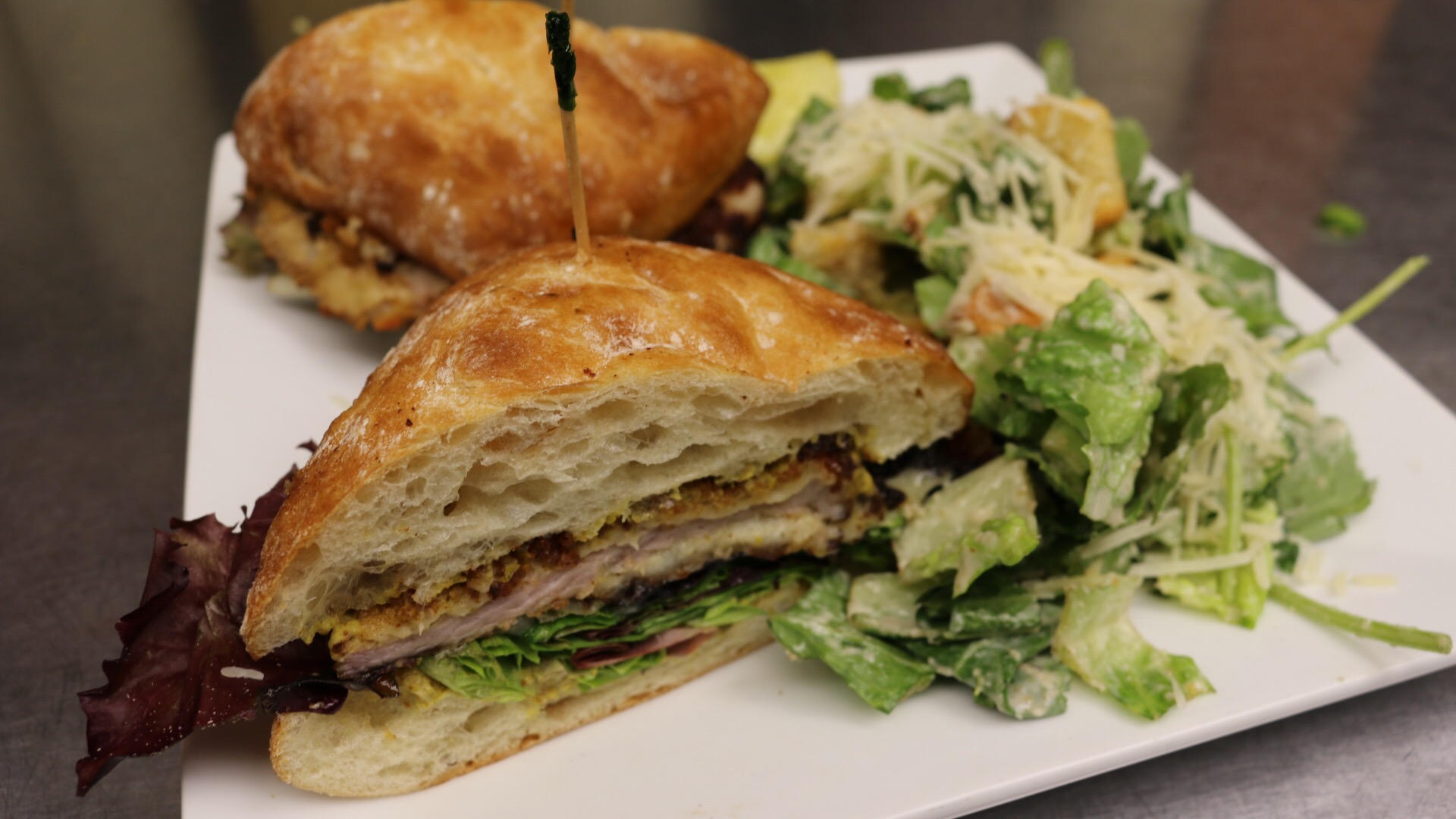the crispy pork sandwich with a small greek side salad