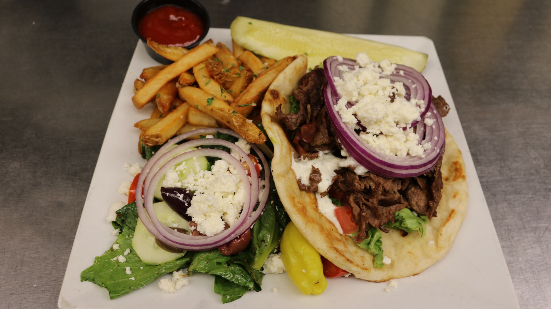 Steak Gyro with rilled steak with lettuce, tomato, cucumbers, red onion and feta, served on pita with tzatziki sauce, garlic fries and a Greek salad.