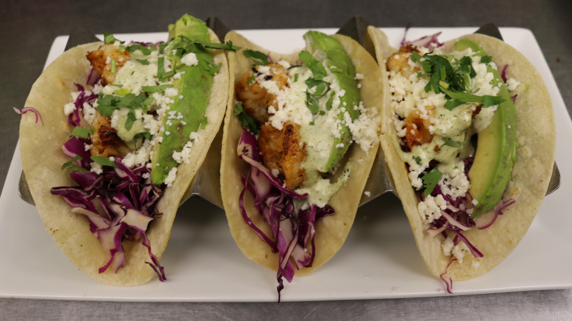 3 fish tacos with avocado, shredded cabbage, and cheese