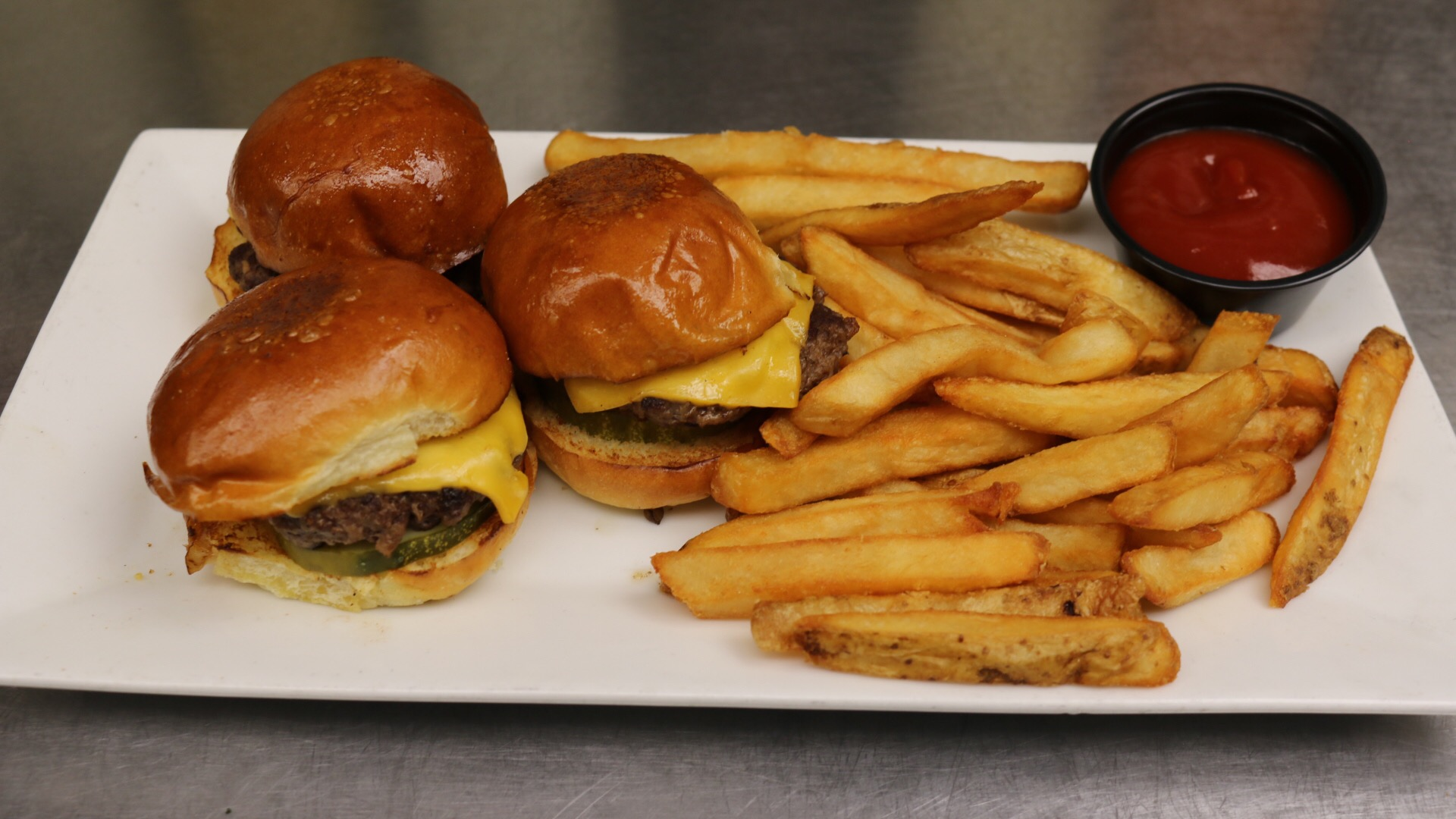 3 cheeseburger sliders with french fries and a side of ketchup